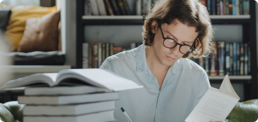 man reading and writing wearing glasses
